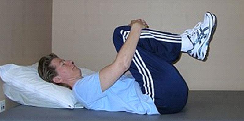 کشش دو زانو به سمت سینه ، ورزش برای مفاصل فاست کمر